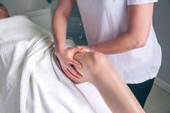 Dé masajes a las manos del terapeuta que hacen el tratamiento linfático del drenaje a la mujer imagenes de archivo