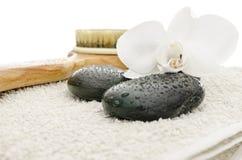 Dé masajes a las piedras, al cepillo y a la orquídea en una toalla Fotografía de archivo