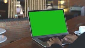 Dé mecanografiar en el teclado del ordenador portátil que muestra la pantalla verde, 4k almacen de metraje de vídeo