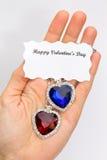 Dé mostrar los corazones rojos y azules de la joyería para la tarjeta del día de San Valentín Fotos de archivo libres de regalías