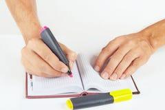 Dé a notas escritas en marcador rojo una libreta en el fondo blanco Imagen de archivo
