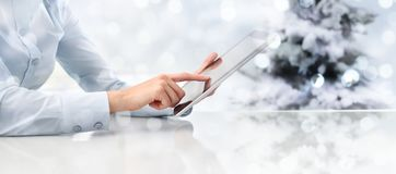 Dé a pantalla táctil la tableta digital en fondo de la Navidad con fotos de archivo