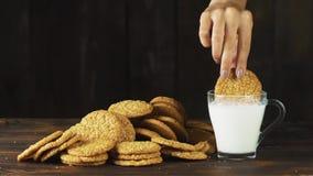 Dé poner una galleta en un vidrio de leche en la cámara lenta Escena cinemática de la comida almacen de metraje de vídeo