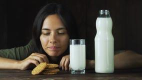 Dé poner una galleta en un vidrio de leche en la cámara lenta Escena cinemática de la comida metrajes