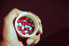 Dé sostener cápsulas de la píldora utilizadas para el concepto médico Imagenes de archivo