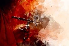 Dé sostener el arma del aerógrafo en proceso de pintura y fondo suavemente borroso de la acuarela Foto de archivo
