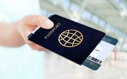 Dé sostener el billete y el pasaporte de avión en aeropuerto Imágenes de archivo libres de regalías