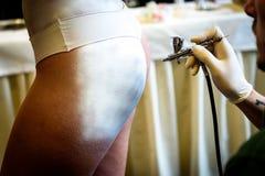 Dé sostener el cepillo de aire en cuerpo de la mujer de la pintura del cuerpo Foto de archivo libre de regalías