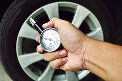 Dé sostener el indicador de presión para la medida de la presión de neumático del coche Imagen de archivo libre de regalías