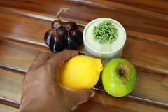 Dé sostener el limón amarillo, las uvas y la manzana verde aislados en el fondo de madera Fotos de archivo