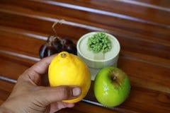 Dé sostener el limón amarillo, las uvas y la manzana verde aislados en el fondo de madera Fotografía de archivo libre de regalías