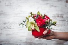 Dé sostener el pequeño florero rojo con el ramo de flores en el espacio gris para el texto Foto de archivo