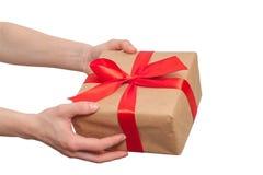 Dé sostener el regalo con el arco rojo aislado en el fondo blanco fotografía de archivo