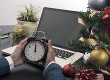 Dé sostener el reloj de medianoche para el día de la Navidad en la oficina Imagen de archivo