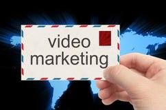 Dé sostener el sobre con la palabra video del márketing en backgro del mundo Imágenes de archivo libres de regalías
