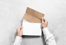 Dé sostener el sobre en blanco blanco y la maqueta doblada del prospecto del arte Foto de archivo libre de regalías
