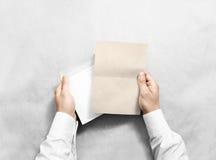 Dé sostener el sobre en blanco y la maqueta de la letra de Kraft, aislados Fotografía de archivo libre de regalías