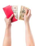 Dé sostener el sobre rojo chino con el dinero aislado sobre el fondo blanco Fotos de archivo