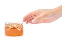 Dé sostener el tarro de la miel aislado en el fondo blanco Imagenes de archivo