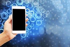 Dé sostener el teléfono elegante sobre el concepto del icono de los engranajes del extracto de ajuste, tecnología moderna fotos de archivo libres de regalías