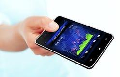 Dé sostener el teléfono móvil con la carta del mercado de acción Foto de archivo libre de regalías