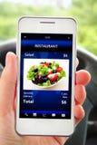 Dé sostener el teléfono móvil con la pantalla de la orden del restaurante Imagen de archivo libre de regalías