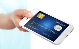 Dé sostener el teléfono móvil con la tarjeta de crédito aislada sobre blanco fotos de archivo libres de regalías