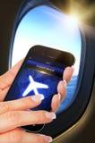 Dé sostener el teléfono móvil con modo del vuelo en el aeroplano imágenes de archivo libres de regalías