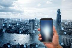 Dé sostener el teléfono móvil en ciudad elegante del tono azul con el fondo de las conexiones de red del wifi