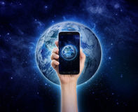 Dé sostener el teléfono móvil o el teléfono elegante en backgro de la tierra del planeta Imagenes de archivo