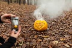 Dé sostener el teléfono y tomar la foto de la calabaza y de la hoja Concepto blogging de Instagram Halloween o día de fiesta de l Fotos de archivo libres de regalías