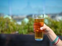 Dé sostener el vidrio de cerveza en un día soleado en el ajuste festivo foto de archivo