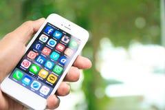 Dé sostener iPhone con medios usos sociales en la pantalla Imagen de archivo