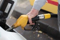 Dé sostener la boca del surtidor de gasolina y rellenar el coche Fotografía de archivo libre de regalías
