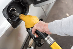 Dé sostener la boca del surtidor de gasolina y rellenar el coche Imagen de archivo libre de regalías