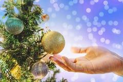 Dé sostener la bola de oro de la Navidad en el árbol de navidad para adornar en día de fiesta, con el fondo de las luces de Bokeh Fotos de archivo