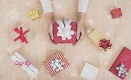 Dé sostener la caja de regalo con las decoraciones y el copo de nieve en de madera Fotos de archivo