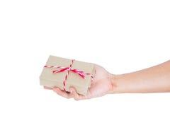 Dé sostener la caja de regalo del paquete postal, aislada en el fondo blanco con el espacio de la copia Fotografía de archivo