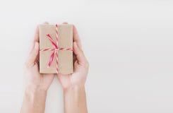 Dé sostener la caja de regalo del paquete postal, en el fondo blanco con el espacio de la copia Fotografía de archivo