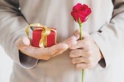 Dé sostener la caja de regalo roja, con la flor color de rosa, tono del vintage Foto de archivo