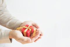 Dé sostener la caja de regalo roja, en el fondo blanco con el espacio de la copia Imagen de archivo