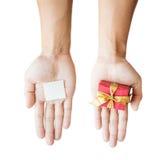 Dé sostener la caja de regalo roja, y la nota del papel en blanco, sobre el fondo blanco Imagen de archivo libre de regalías