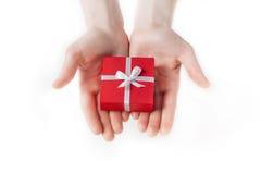 Dé sostener la caja para un regalo aislado en blanco imagenes de archivo