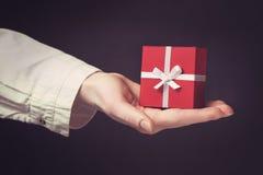Dé sostener la caja para un regalo aislado en negro Imagen de archivo libre de regalías
