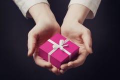 Dé sostener la caja para un regalo aislado en negro Fotografía de archivo libre de regalías