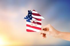 Dé sostener la casa de papel en colores de la bandera americana imagen de archivo libre de regalías
