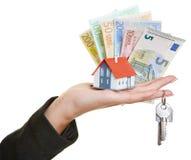 Dé sostener la casa, llaves, dinero euro Imagen de archivo libre de regalías