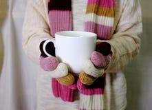 Dé sostener la leche caliente con los guantes blancos del suéter, de la bufanda y de la mano Foto de archivo libre de regalías