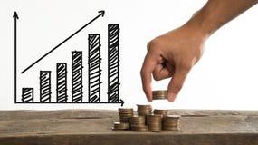 Dé sostener la moneda con el gráfico del darw, el ahorro y el concepto del efectivo Imagen de archivo