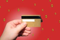 Dé sostener la tarjeta de crédito en el fondo rojo fotos de archivo